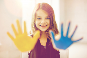 happy girl showing painted hand palms